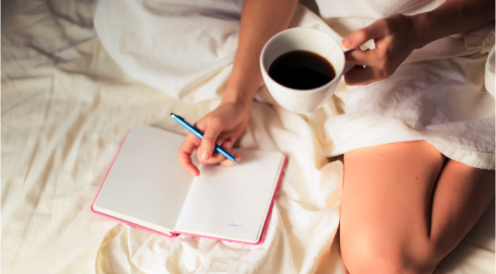 A woman in bed with a cup of coffee writing in a notebook. An example of staying positive while at home.